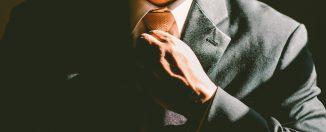 homme en costume ajustant sa cravate