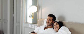 Jeune couple qui se prélasse au lit en peignoir