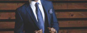 homme portant un costume bleu marine, une chemise blanche et une cravate bleue