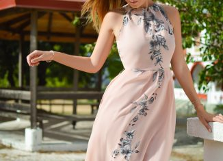 femme portant une robe fluide rose pâle à fleurs