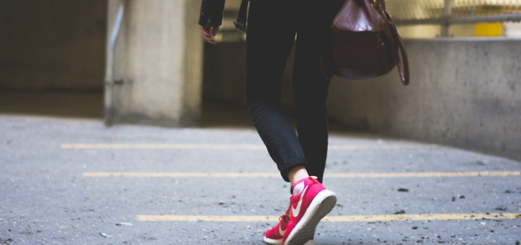 vue sur les pieds d'une femme portant des baskets rouges et un pantalon noir