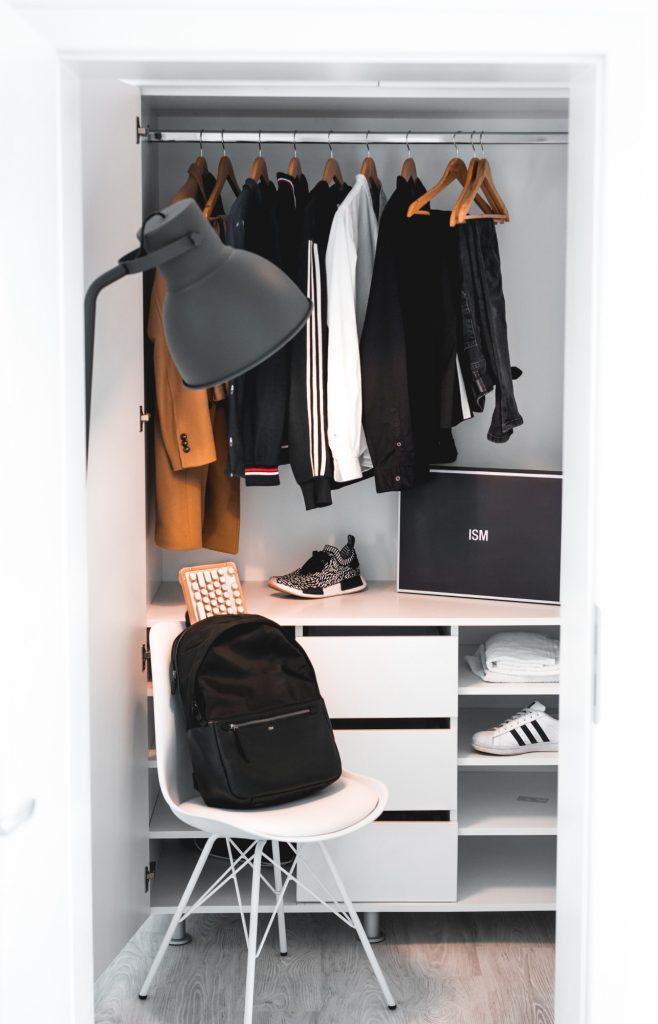 dressing avec vêtements suspendus chaussures et un sac à dos posé sur une chaise