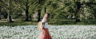femme au look bohème qui marche dans les fleurs